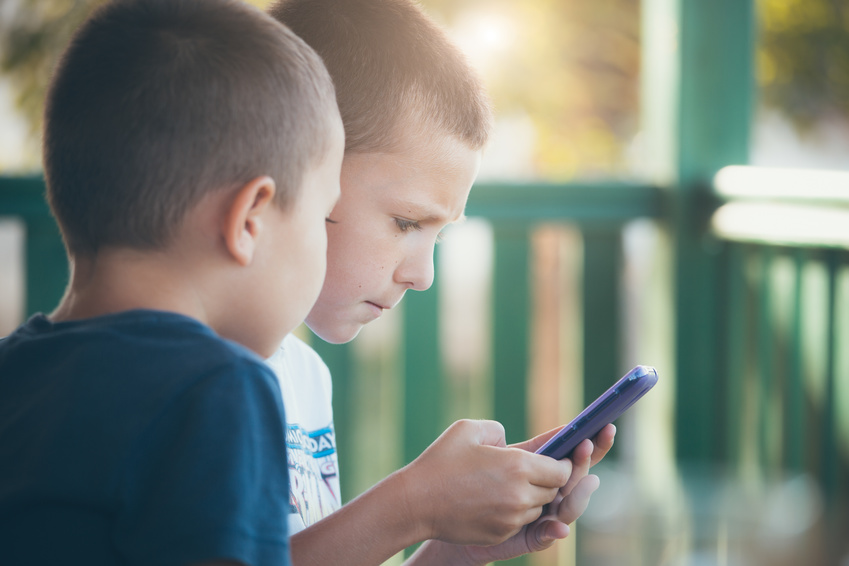 Two little boys playing games on mobile phone